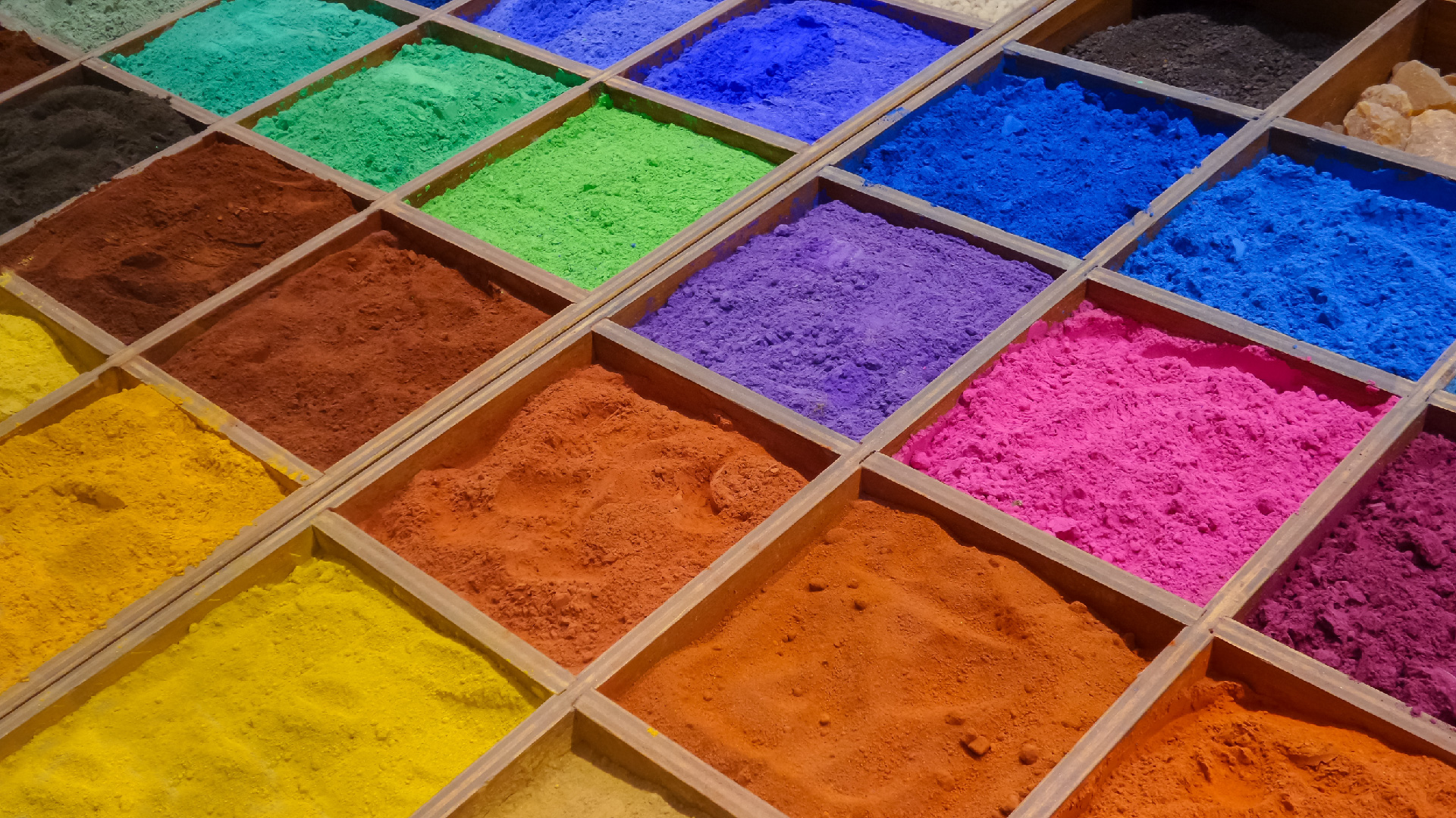 Bright, colorful pigment powders in a grid