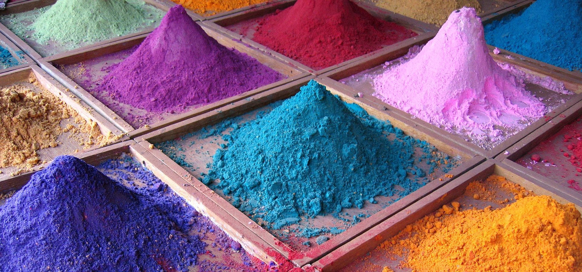Colorful piles of pigment powder in a grid